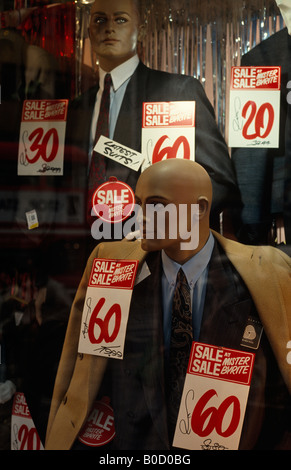 Mannequins wearing bargain office suits and coats fill a Mr Byrite mens' cheap clothes shop window during a sale - Stock Photo