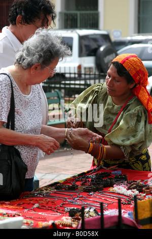 Kuna indian woman selling chaquiras at a street market of Panama City - Stock Photo