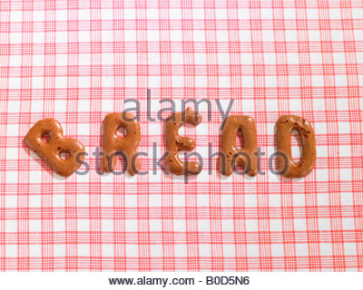 Word BREAD on a tablecloth made from alphabet biscuits - Stock Photo