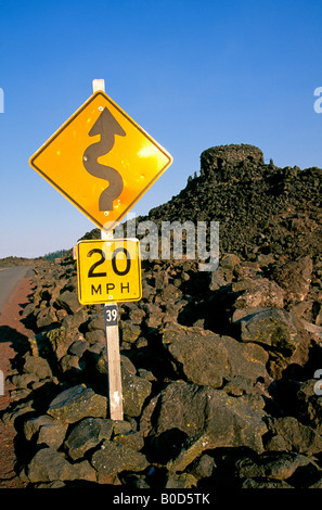 A road sign warns drivers of a curvy road through an alpine lava flow on the McKenzie Pass Scenic Byway - Stock Photo