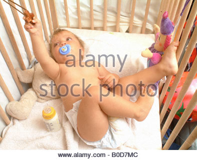 Baby in cot crib toy - Stock Photo