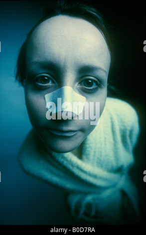 WOMAN FACE WITH ADHESIVE PLASTER BANDAGE OVER NOSE - Stock Photo