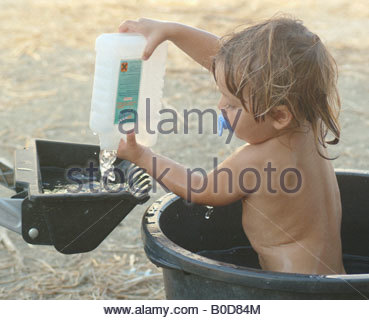 Baby little boy playing outside in the garden park yard grass fun play games game human young summer happy happiness - Stock Photo