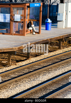 A young woman waits for her outbound train. - Stock Photo