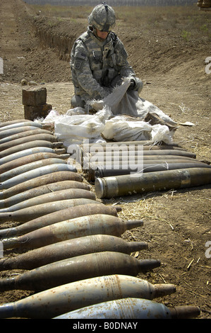 A U S Army soldier examines the contents of a bag from a discovered weapons cache outside Abu Thayla Iraq on April - Stock Photo