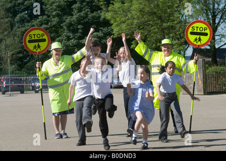 Two lollipop ladies with children running and jumping from the school they help out at. - Stock Photo