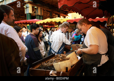 Making purchases at food stalls in Borough Market, London, England. - Stock Photo