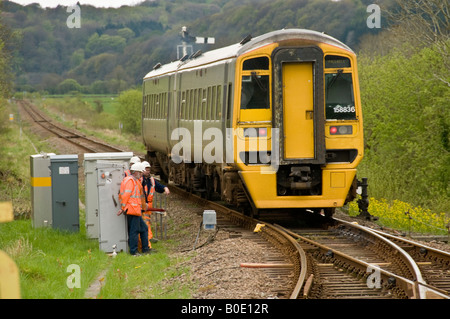 Arriva Wales DMU train on the single track Cambrian Coast line passing a group of engineers who are working on the - Stock Photo