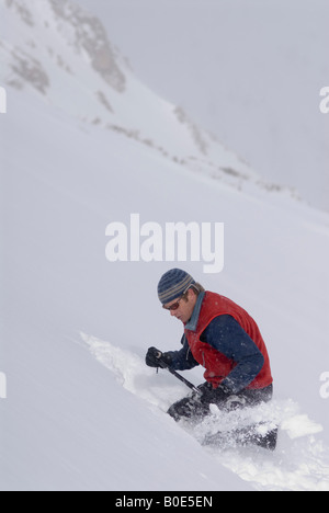 backcountry skier digging an avalanche pit in the snow- testing the snowpack for safety before skiing - Stock Photo