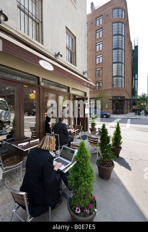 Woman working on a laptop computer outside a restaurant on Greenwich Street, Tribeca, Manhattan, New York City - Stock Photo