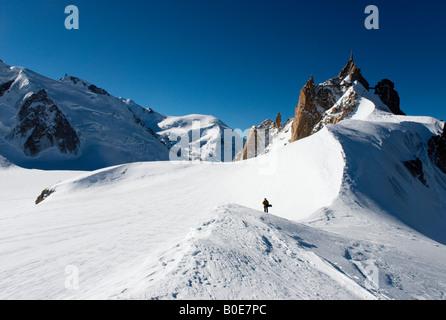 Snowboarder walking on ridge towards Grand Envers du Plan variant of Vallée Blanche, Aiguille du Midi in background - Stock Photo