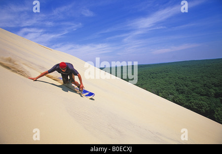 Sandboarder racing down huge dune - Stock Photo