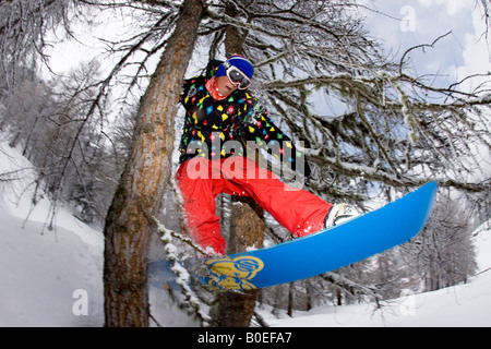 Snowboarder Jo Howard riding through a tree gap of piste in Tignes, France. - Stock Photo