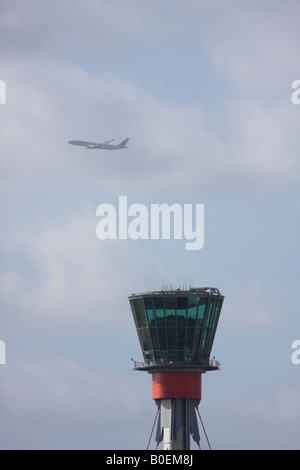 Air control tower and passenger airplane flying out of London Heathrow in the background. - Stock Photo