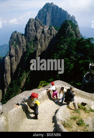 Chinese climbers pass foreign photographer on steps up Lotus Flower Peak, with Jade Screen Terrace & Celestial Capital - Stock Photo