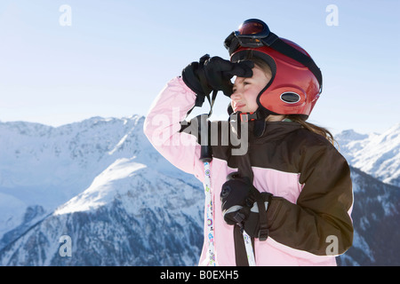 Young girl in ski kit looking at scenery - Stock Photo