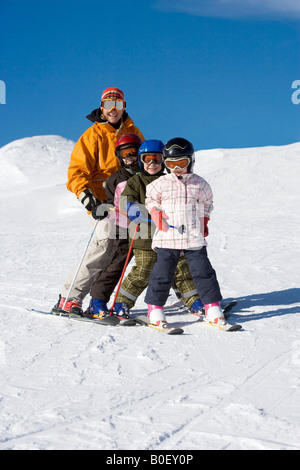Mother skiing with children - Stock Photo