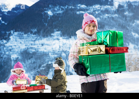 Children with presents in the snow - Stock Photo