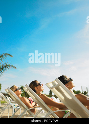 Three ladies relaxing in the sun - Stock Photo