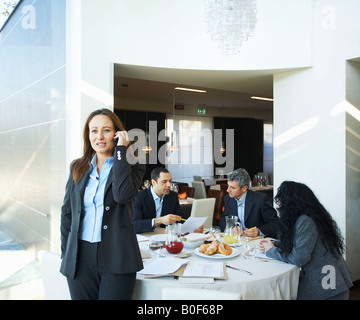 Businesswoman on phone during meeting - Stock Photo