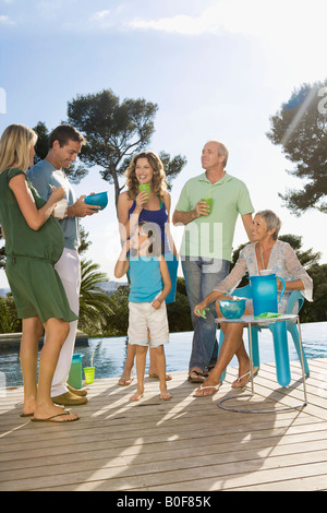 Family on a wooden terrace by a pool - Stock Photo
