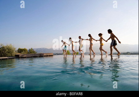 People walking by a pool, holding hands - Stock Photo