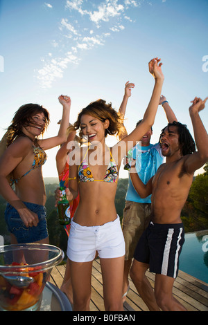 Young people dancing on terrace by pool - Stock Photo