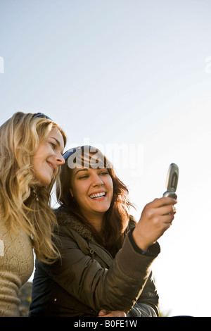 Two girls looking at mobile together - Stock Photo