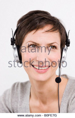 Woman with headset smiling - Stock Photo
