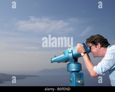 Man looking through spyglasses - Stock Photo