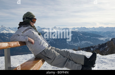 Snowboarder sitting on bench - Stock Photo
