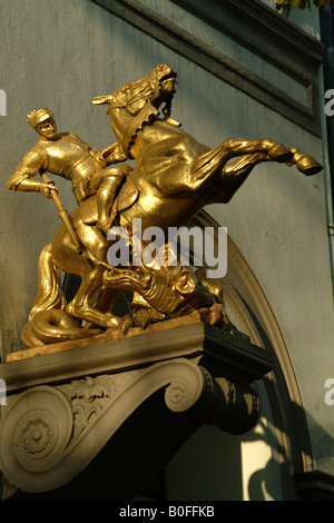 Golden statuette of St. George and the dragon on a pharmacy facade in Lange Reihe, shopping lane in St. Georg, Hamburg, - Stock Photo