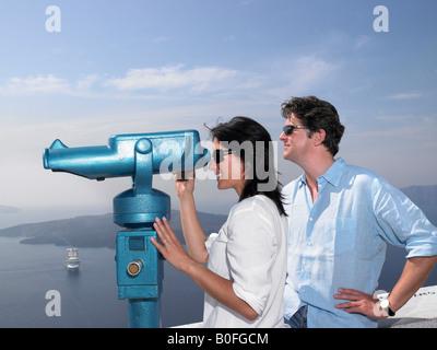 Couple looking through spyglasses - Stock Photo