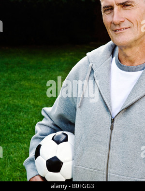 Man holding football, portrait - Stock Photo