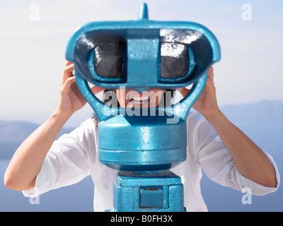 Woman looking through spyglasses - Stock Photo