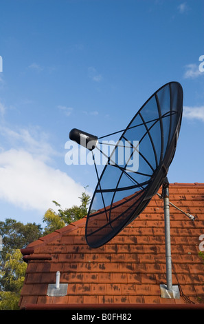 A satellite dish on a red tile roof points towards the sky in Australia - Stock Photo