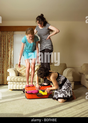 Three females trying to close suitcase. - Stock Photo