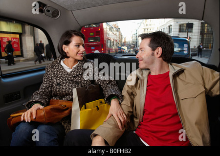 Couple in London taxi with bags - Stock Photo