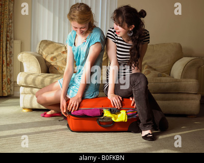 Two females trying to close suitcase - Stock Photo