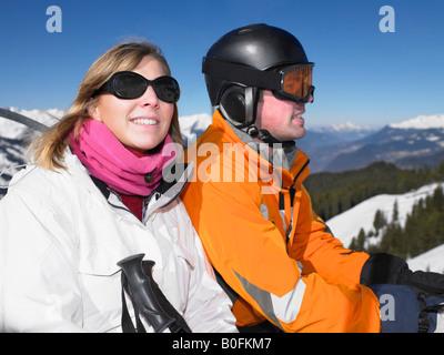 Smiling couple on ski lift - Stock Photo