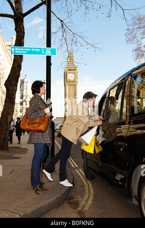 Couple with London taxi, Big Ben behind - Stock Photo