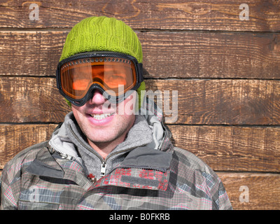 Young man in goggles and snow gear - Stock Photo
