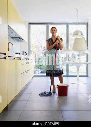 Young woman with mop in kitchen - Stock Photo