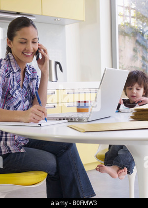 Woman working at home, son at table - Stock Photo