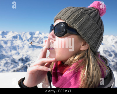 Young woman smoking in snow gear - Stock Photo