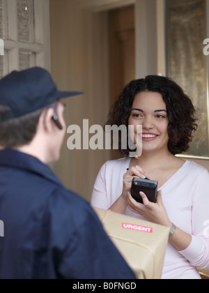 Woman signing for package with courier - Stock Photo