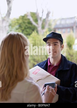 Courier and recipient in doorway - Stock Photo