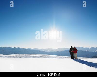 Couple walking in snow on mountain top - Stock Photo