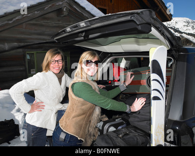 Young women packing car - Stock Photo