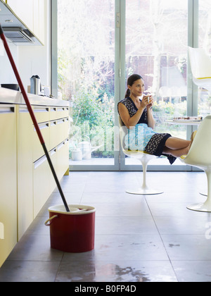 Young woman relaxing, mop in foreground - Stock Photo